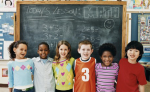 Children standing in front of a chalkboard - League of Education Voters