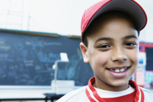 Portrait of a boy smiling in a classroom --- Image by © Andersen Ross/Blend Images/Corbis