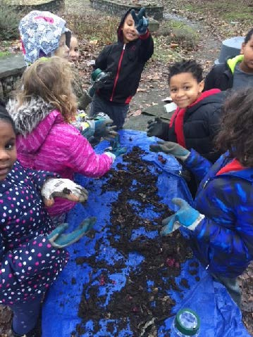 Tilth Alliance facilitates project-based learning with South Shore Students. Six children crowd around a blue tarp with dirt and critters on it. The children are in winter clothes.