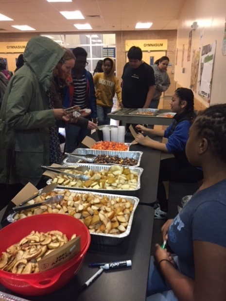 Tilth Alliance facilitates project-based learning with South Shore Students. 8 students line along a table with different samples of Washington produce.